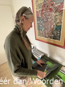Marjan de Kort bezig foto's op maat te snijden voor ansichtkaarten verkoop en expositie