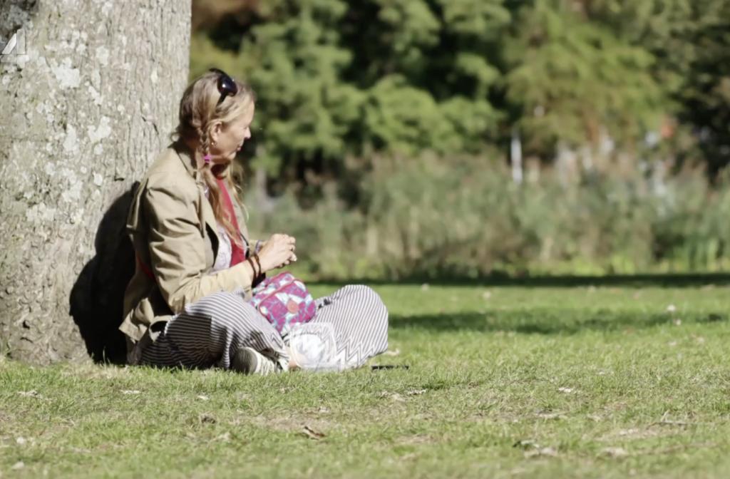 een vrouw die met zonnig weer in het Vondelpark in Amsterdam tegen een boom zit en wel mijn tweelingzus lijkt, mijn evenbeeld, mijn dubbelganger